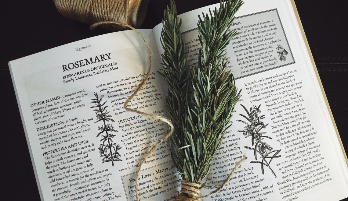 a book and sprig of herb showing the uses and benefits of rosemary