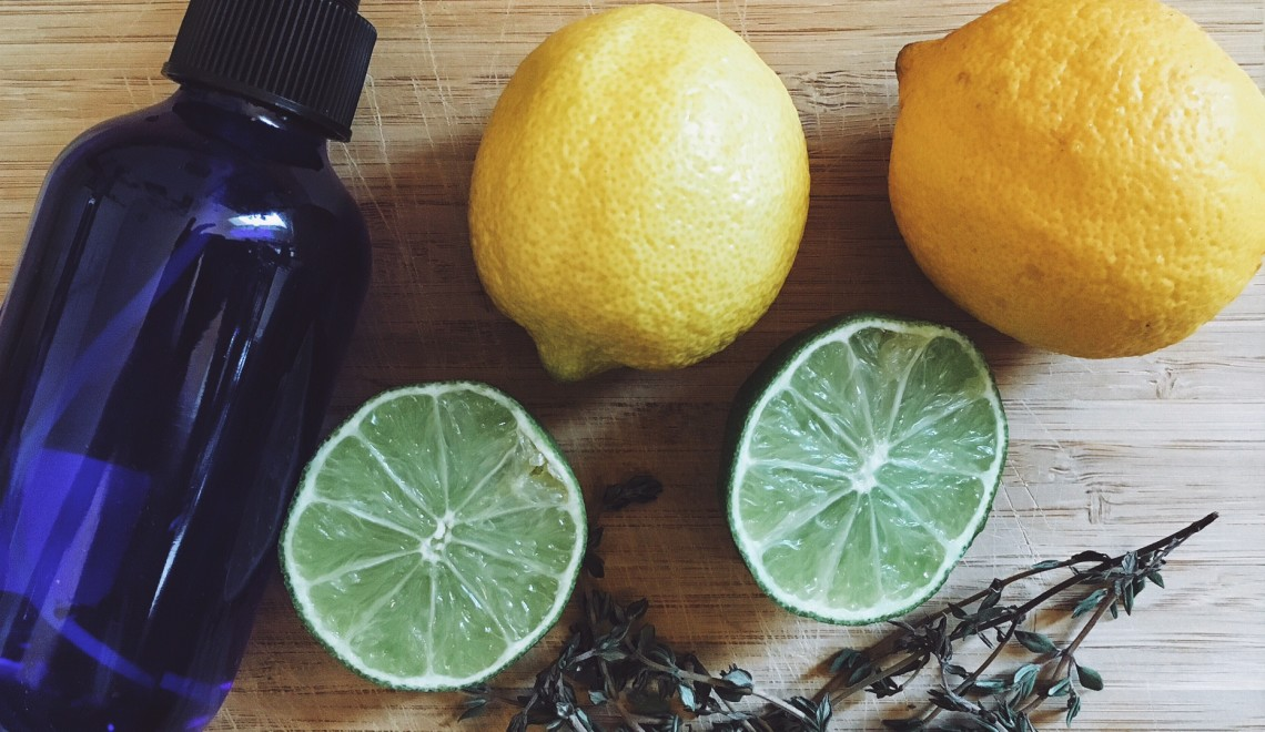 Lemons, limes and thyme on wood cutting board with spray bottle