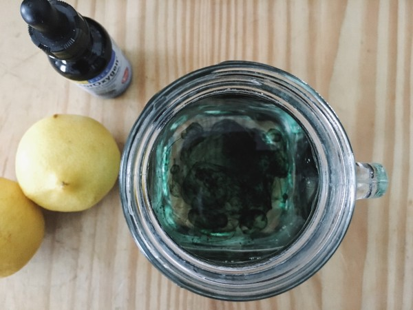 Lemons and liquid chlorophyll bottle on cutting board with a glass of water