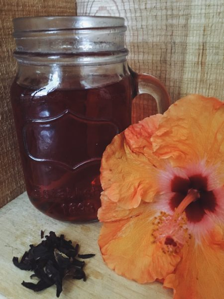 Glass of Hibiscus tea next to a Hibiscus flower and dried petals