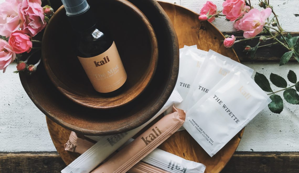 Kali organic tampons, wipettes and rosewater mist on wood plate surrounded by pink roses