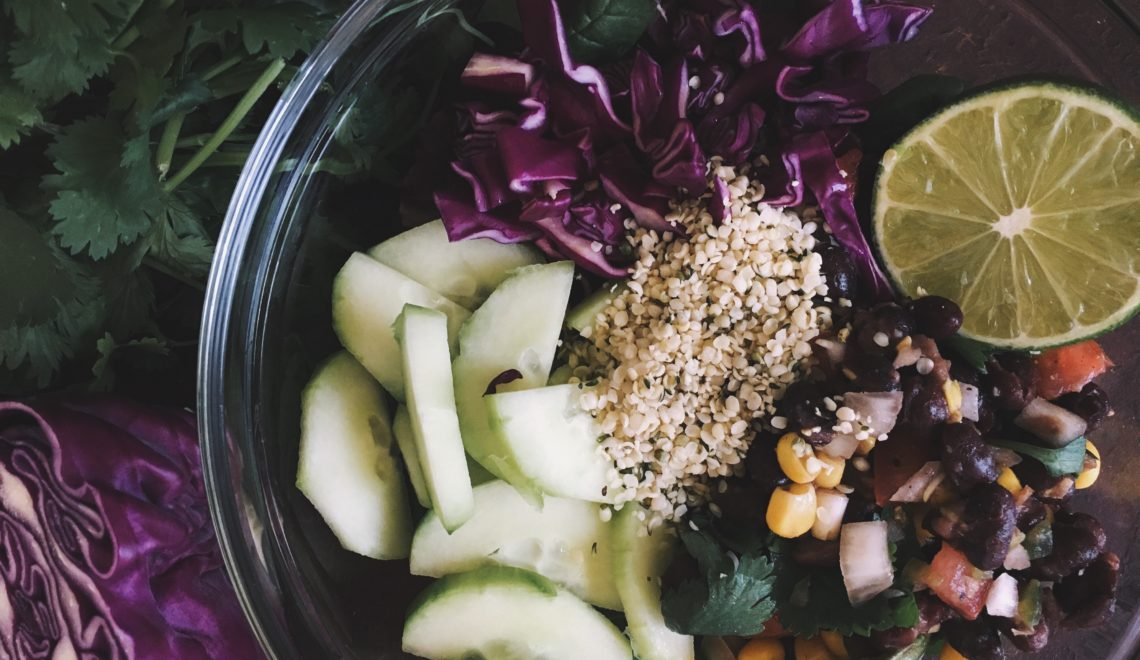 Organic salad in a bowl with cucumber, purple cabbage, hemp seeds, lime and black bean salsa
