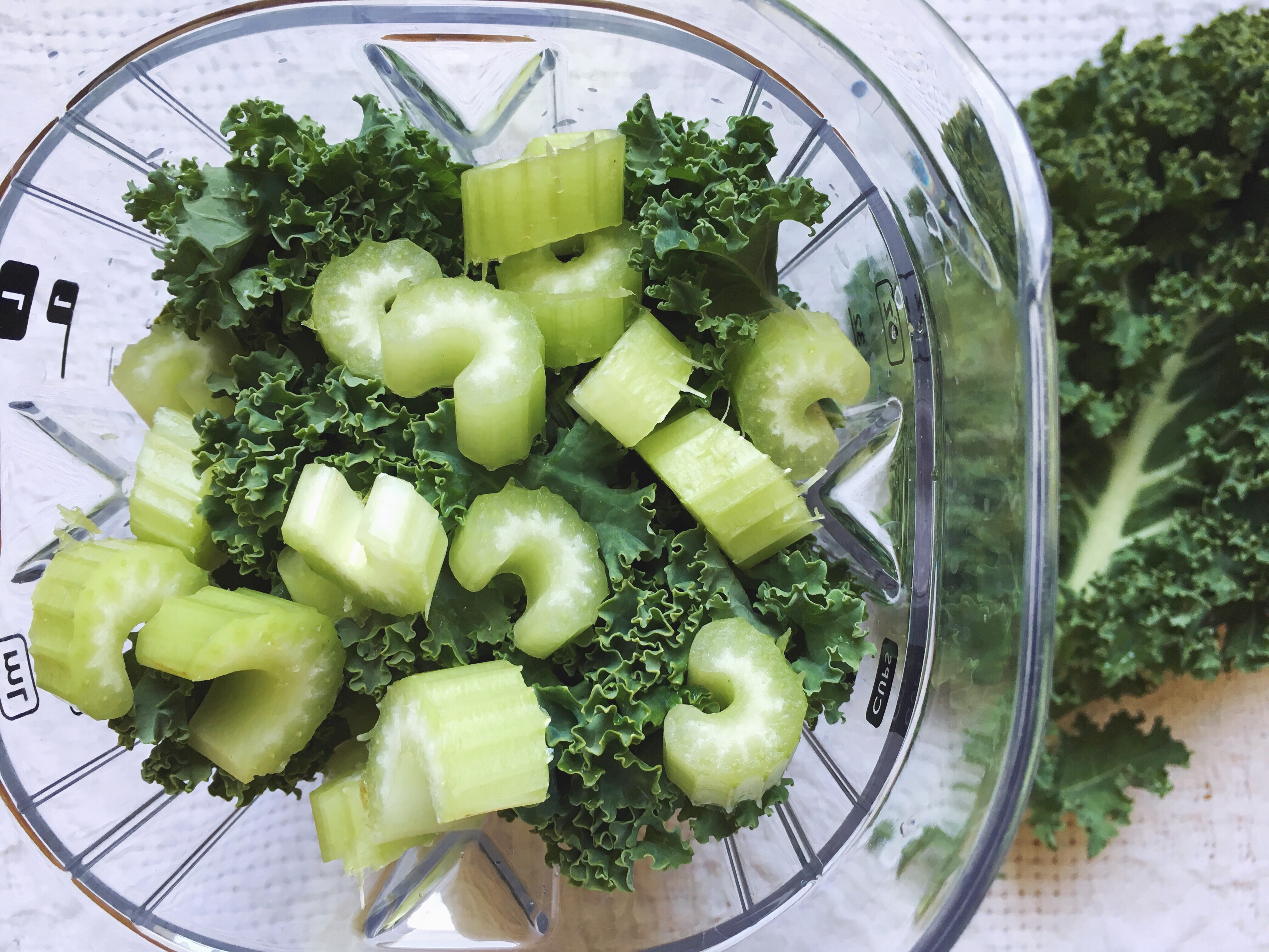 chopped celery and kale in a blender. ingredients in a anti-inflammatory smoothie